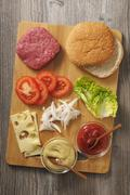 Ingredients for a cheeseburger on a chopping board Stock Photos
