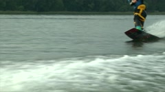 Young man hanging out on a wakeboard sport boat in the summer Stock Footage