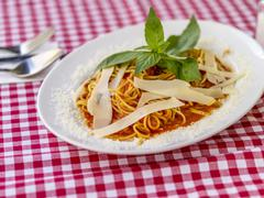 Spaghetti with tomato sauce and Parmesan cheese on a checked tablecloth Stock Photos