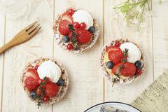 Strawberry tartlets with blueberries, redcurrants and cream (seen from above) Stock Photos
