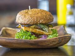 A burger on a wooden dish on a restaurant table Stock Photos