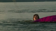 Girl floats in pond water with wakeboard, summer sunset Stock Footage