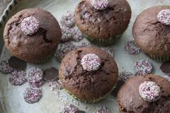 Chocolate and cherry muffins decorated with chocolate jazzies Stock Photos
