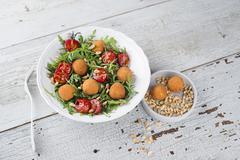 Rocket salad with tomatoes and crispy mozzarella balls Stock Photos