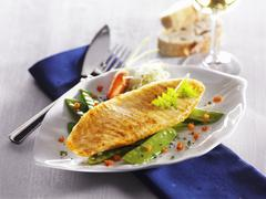 Catfish fillet on a bed of mange tout and carrots on a ceramic plate Stock Photos