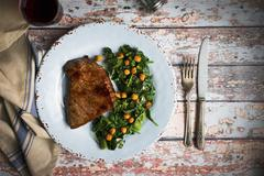 Beef steak with a chickpea and spinach medley Stock Photos