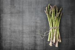 A bundle of asparagus on a grey surface Stock Photos