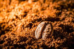 A coffee bean in ground coffee Stock Photos