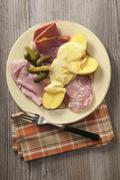 Raclette potatoes with various types of cold meat and gherkins Stock Photos