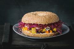 A bagel with carrots, blue cheese and beetroot sprouts Stock Photos