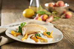 Brook trout with a white sauce, apricots, spinach and diced potatoes Stock Photos