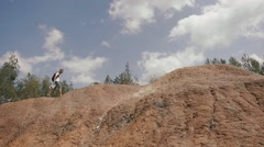 Young male tourist walks on rocky hills in mountains checking his way with paper Stock Footage