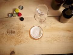 Beer glasses, beer bottle caps and beer bottles on a wooden surface Stock Photos