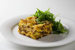 Lasagne with a rocket salad Stock Photos