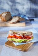 A sandwich on a light blue napkin on a wooden board with a sliced loaf of bread Stock Photos