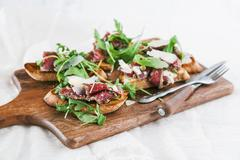 Crostini with carpaccio, rocket, capers and pecornio romano cheese Stock Photos