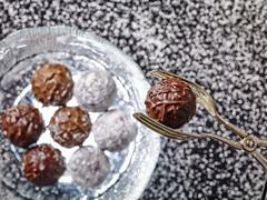 Praline tongs holding a truffle praline over a glass plate of various truffles Stock Photos