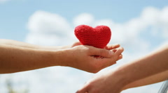 Man and woman holding red heart in their hands. Sunny day. Stock Footage