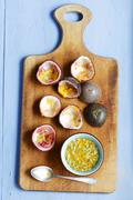 Hollowed out passion fruit shells and a bowl of fruit Stock Photos