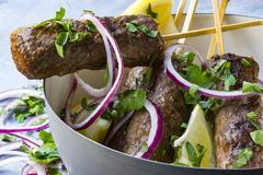 Cevapcici on wooden skewers with onions, parsley and lemon in a grey bowl Stock Photos
