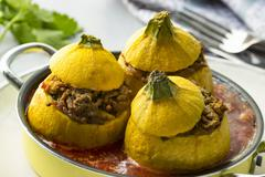 Yellow squash filled with minced meat and tomato sauce and cutlery Stock Photos