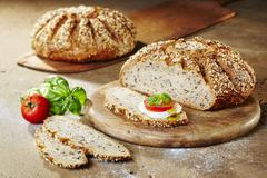 Two loaves of multigrain quark bread with tomatoes, mozzarella, basil and olive Stock Photos