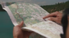 Man's hand drawing on map by finger, checking way when looking to lake ahead Stock Footage