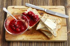 Toast with cherry jam and butter Stock Photos