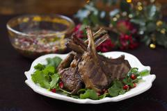 Grilled lamb chops on rocket with pomegranate seeds Stock Photos
