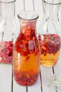 Freeze-dried strawberries and vinegar in preserving bottles Stock Photos
