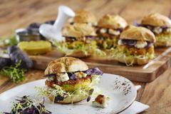 Mini veggie burgers with polenta patties, feta cheese and various types of Stock Photos