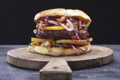 A burger with onions, bacon and apples on a wooden board Stock Photos