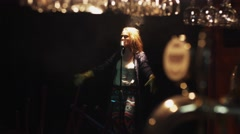 Scrubwoman in gloves sing on stage in vintage microphone under spotlight. Dance Stock Footage