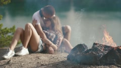 Loving teenager couple embraces while relaxing at campsite on forest rivershore Stock Footage