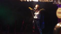 Scrubwoman sing on stage in microphone under spotlight. Scream. Shake hair Stock Footage
