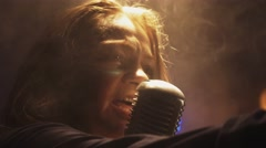 Scrubwoman in gloves sing in vintage microphone on stage. Smoke. Spotlight Stock Footage