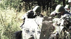 Soldiers move a anti tank gun through a meadow Stock Footage