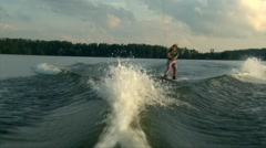 Wakeboarder girl make wave to wave trick on pond water, golden sunset Stock Footage
