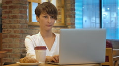 Young beautiful businesswomen enjoying coffee during work on laptop. Stock Footage