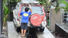 Thai man washing car at local carwash station in Nonthaburi, Thailand Stock Footage