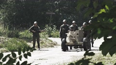 Soldiers moving a anti tank gun forward on a battlefield – light smoke Stock Footage