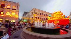 CROWDS PEOPLE SIT ROUND SENADO SQAURE MACAU CHINA Stock Footage