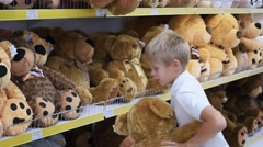 A child plays with a soft toy in the shop Stock Footage