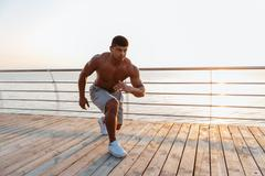 Shirtless african young sportsman working out on pier Stock Photos