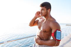 Serious african young sportsman talking on the phone outdoors Stock Photos
