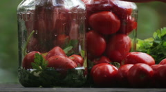 Composition of tomatoes. Hand puts the tomatoes in a jar. Stock Footage