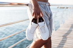 Cropped image of sportsmen hands holding sneakers at pier Stock Photos