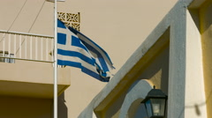 Greek flag waving in a wind on poles by the balcony of the building facade Stock Footage