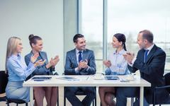 Business team with laptop clapping hands Stock Photos