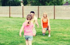 Happy family playing outdoors Stock Photos